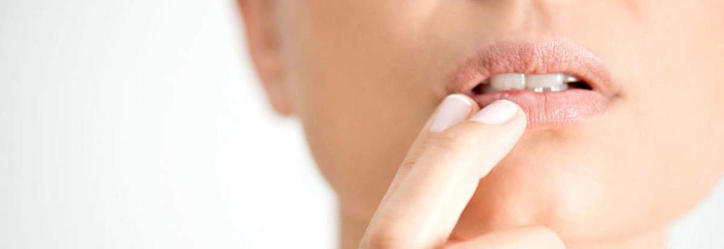 mulher tocando com dois dedos o lábio ressecado