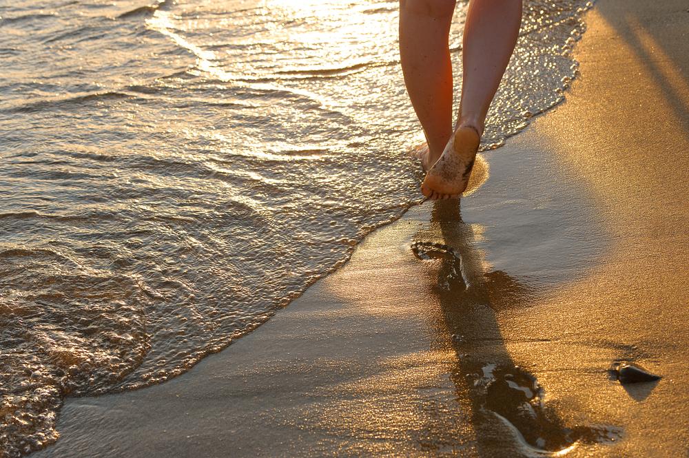 mulher caminhando na areia beira da praia