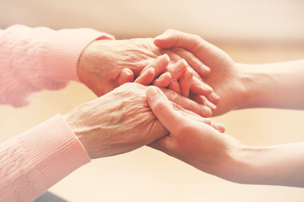 mulher segurando mãos de senhora idosa