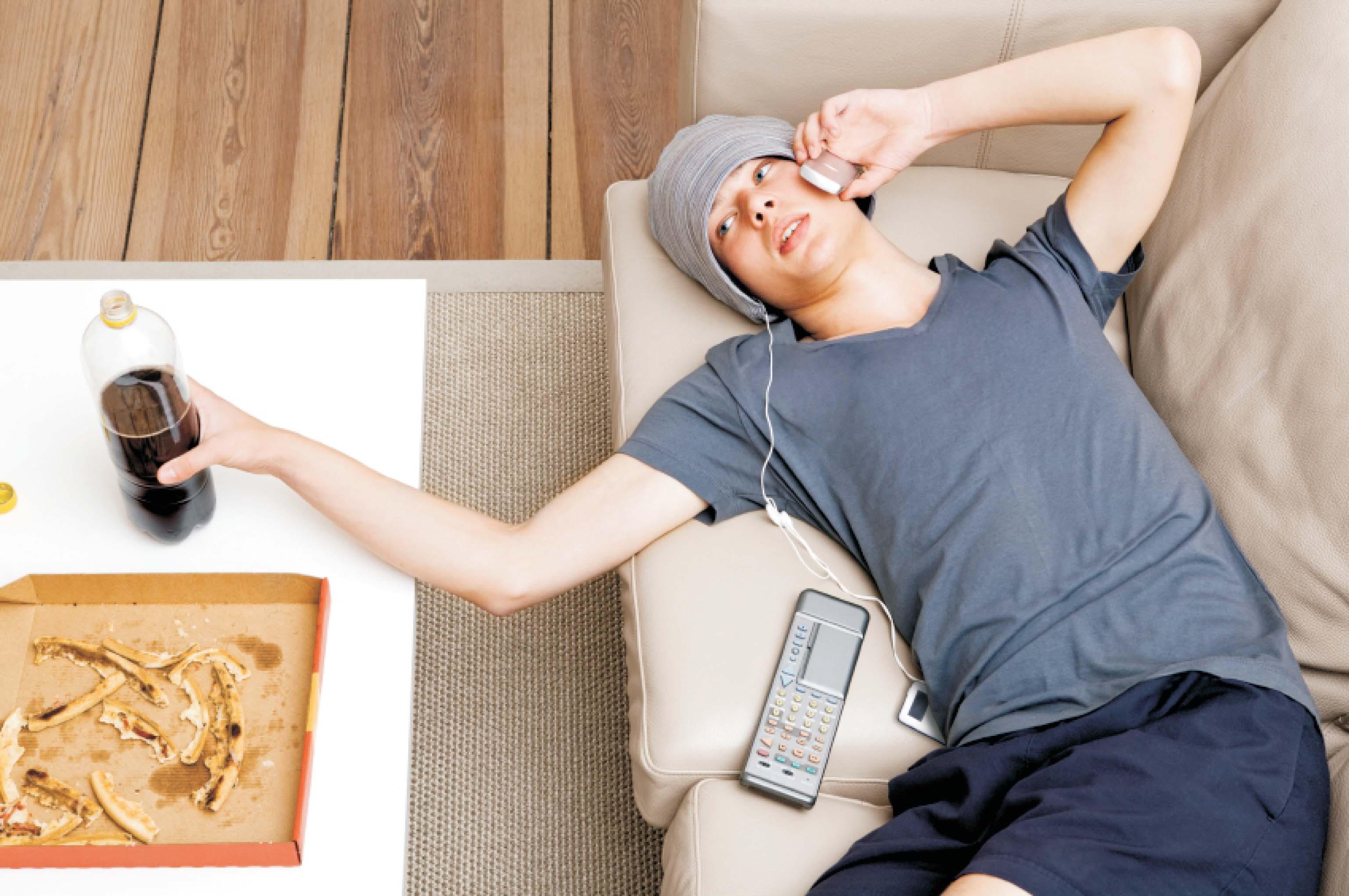 Sedentarismo: Conversando no celular deitado no sofa class=