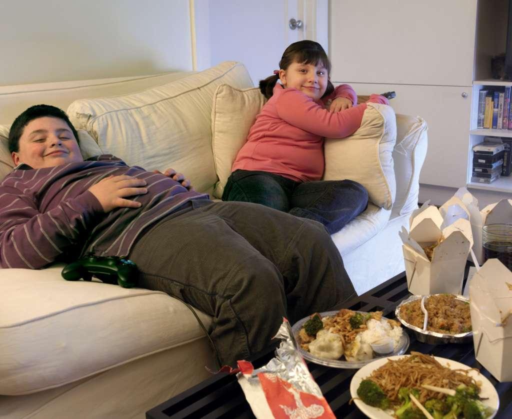 crianças com obesidade em sofá cheio de comida