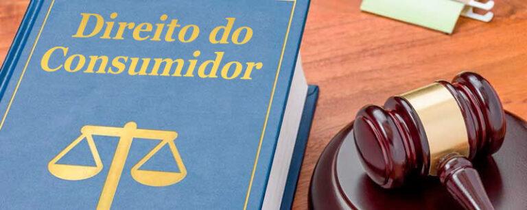 livro direio do consumidor, martelo de juiz, mesa