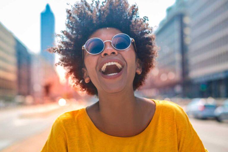 Plano coletivo por adesão: Foto de mulher negra com camisa amarela e óculos escuros rindo em uma avenida
