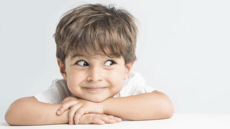Plano de saúde para criança: foto de um menino sorrindo e apoiando sua cabeça sob suas mãos cruzadas em uma mesa