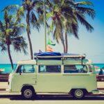 Planos de saúde: Foto de Kombi branca parada na orla de uma praia em um dia ensolarado