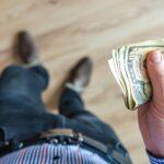 Um homem segurando algumas notas de dinheiro americano